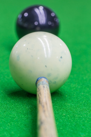 Selective focus on cue and white snooker ball dirty blue chalk powder with blurred black snooker ball, billiard playing.