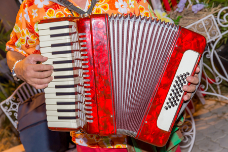 A man wears colorful shirt and plays the red accordion, the street musician. Stock Photo