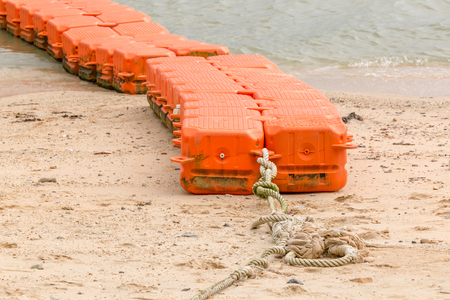 safe water: Close up end of orange sea buoys tied on sea beach, marine equipment for marking safety zone.