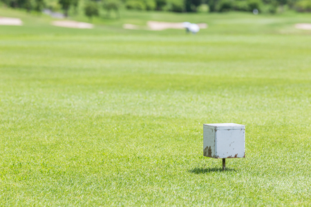 off course: Close-up white color wooden tee off area or tee box with blurred natural green golf course in background. Stock Photo
