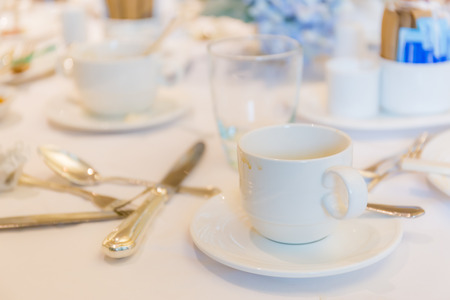 Blurred photo of used coffee cups placed on lunch table after completed mealtime. Stock Photo