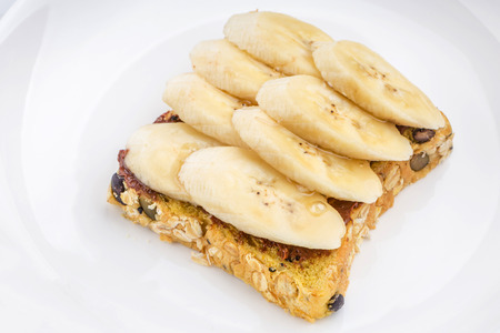 buttered: Chocolate and sliced banana on open wholewheat sandwich bread topped with honey served in white plate, healthy eating concept.