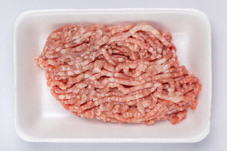 veal sausage: A white foam tray of raw minced pork from supermarket, fresh food ingredients concept. Stock Photo