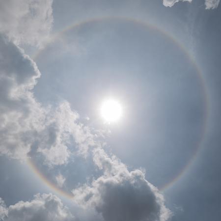 背景には、自然現象の曇り空で太陽ハロー (光学現象)。