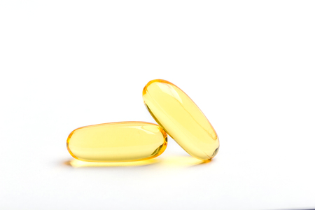 Two yellow soft gelatin capsules contain of fish oil supplement, isolated on white background.