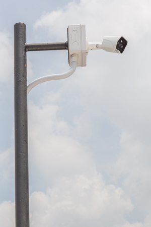 Security camera, CCTV is installed for monitoring on building with blurred blue sky in background