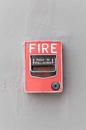 Red fire alarm switch on exterior cement wall of commercial building, safety concept.