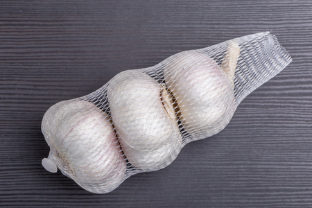 Packaged white garlic bulbs in net place on wooden table, general and useful seasoning for tasty foods. Фото со стока