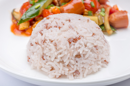 Close-up stream brown rice with blurred background of fried sausages and mixed vegetables in ketchup sauce, healthy eating concept. Фото со стока