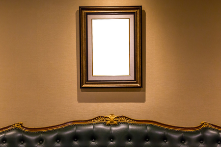The blank luxury photo frame hanging on wall above the sofa, interior decoration concept.