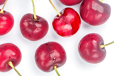 Close up fresh and refrigerated cherries and water drops on white background.