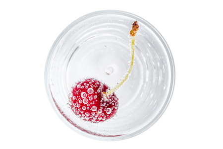 The red cherry and bubbles in sparkling soda water on white background, refreshment beverage. Фото со стока