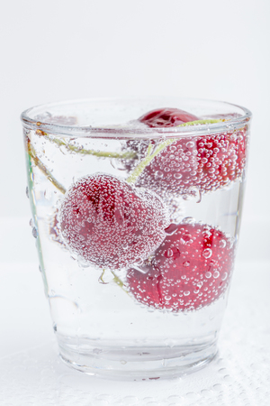 The sweet ripe cherries in a glass of sparkling soda water placed on white background, healthy drinking concept. Фото со стока
