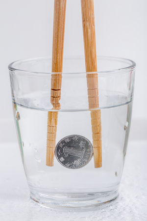 Japanese coin (yen) holding by wooden chopsticks in a glass of water isolated on white background, currency exchange concept.