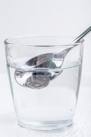 Japanese coin (yen) is picking up by silver spoon from a glass of water isolated on white background, financial concept.