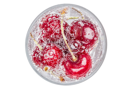 Ripe and sweet cherries in a glass of sparkling soda water placed on white background, healthy drinking concept.