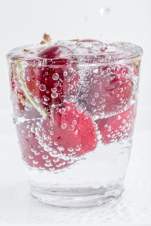 Group of sweet ripe cherries and bubbles sparkling in a glass of soda water placed on white background.