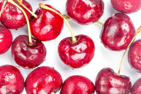 Refrigerated juicy cherries with iced water drops spread around white background, healthy eating concept. Фото со стока