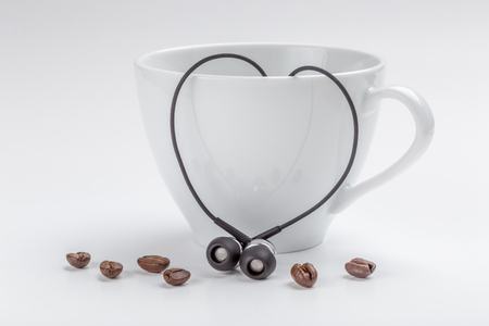 White coffee cup, coffee beans and heart-shape black headphones on white background, love concept. Фото со стока