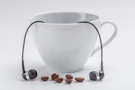 White coffee cup, coffee beans and black headphones on white background, relax time concept.