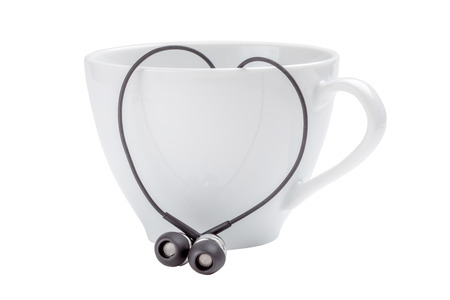 White coffee cup and heart-shape of black headphones on white background, love concept. Фото со стока