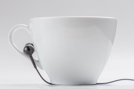 Detail of white coffee cup and black headphones on cup holder on white background, relax time concept.