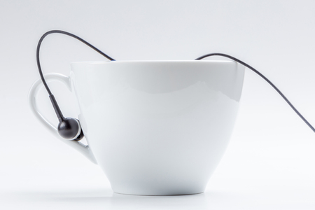 Detail of white coffee cup and black headphones on cup holder isolated on white background, relax time concept.