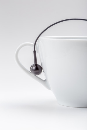 Half white coffee cup and black headphones on cup holder on white background, relax time concept.