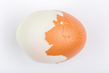 Peeled hard shell boiled egg isolate on white background. Фото со стока