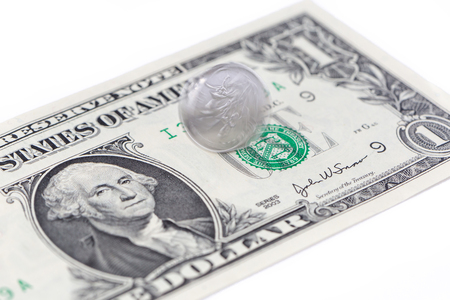 Motion spinning China coin on one US dollar bill on white background, Chinese and USA economy finance concept.