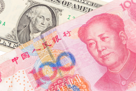US dollar bill and Chinese yuan banknote on white background, USA and Chinese exchange rate concept. Фото со стока