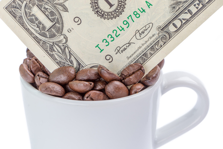 Detail of one US dollar banknote in a cup of coffee beans on white background.