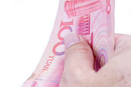 Detail of male hand holding hundred Chinese RMB banknotes on white background, business and finance concept. Фото со стока
