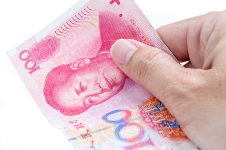 Detail of male hand holding hundred Chinese RMB banknotes on white background, business and finance concept. Stock fotó