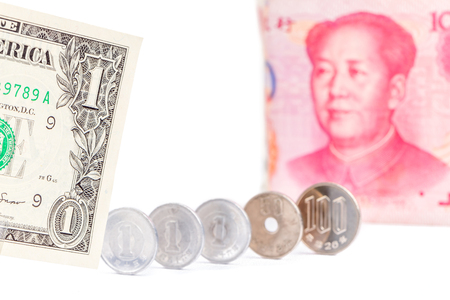 One US dollar bill with blurred Chinese yuan banknote and Japanese yen coins on white background, world economy concept.