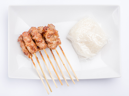 Grilled pork skewers served with stream sticky rice on white plate, traditional Thai traditional food. Stock fotó