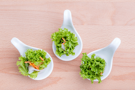 Small serves of fresh vegetable salad spring roll on wooden board background, Asian healthy appetizer dish.