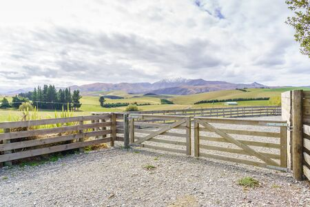 Closed wooden farm gate at the entrance to a farm in the high country with meadow and mountains background in mid Canterbury New Zealand South Island