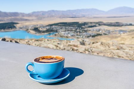 Latte art Coffee in blue cup with a amazing view from Mt john, Lake Tekapo, New Zealand