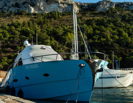 blue boat moored to the dock in mediterranean sea