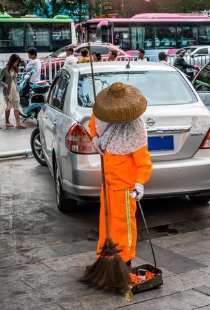 trash the dress: Woman in Eastern dress, sweeping the street. Streets around Jiefang Road, Sanya. Hianan. China.