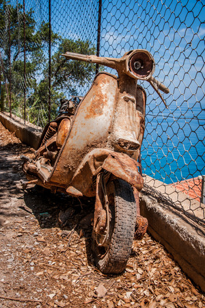 lean over: Rusty scooter on the coast