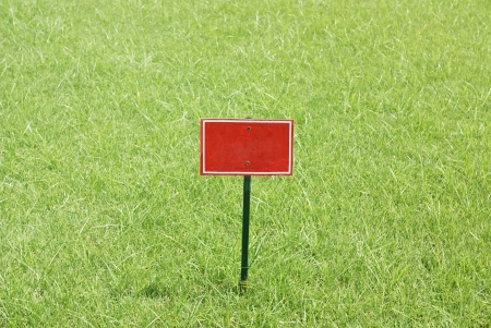 disallow: Red metal blank billboard stabbed in greensward Stock Photo