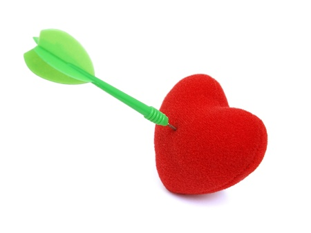 Red heart stabbed by green dart on white background