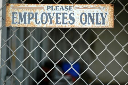 A Rusty Employees Only Sign on a Chain Link Fence at an Abandoned Industrial Building photo
