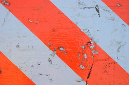 Background Texture of a Dirty and Scratched Orange and White Striped Stop Sign photo