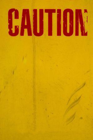 A Dirty, Grungy Yellow Caution Sign With Red Text and Copy Space photo