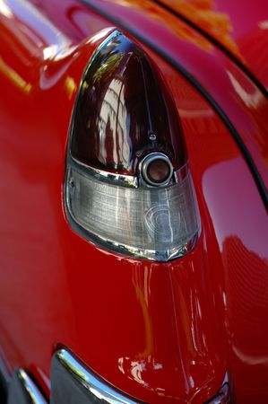 Detail of a Taillight of a Shiny, Red Classic American Car photo