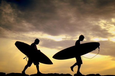 walk board: Vacation Silhouette Of Two Surfers Carrying Their Boards Home At Sunset