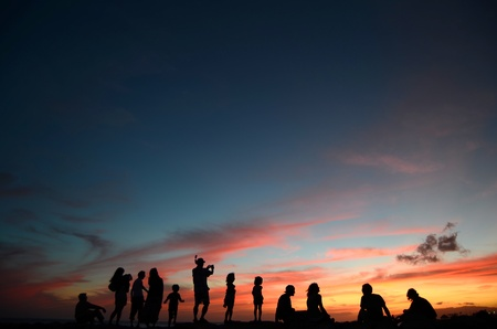 hawaii sunset: A Group Of People Enjoying A Sunset By The Beach In Hawaii Stock Photo